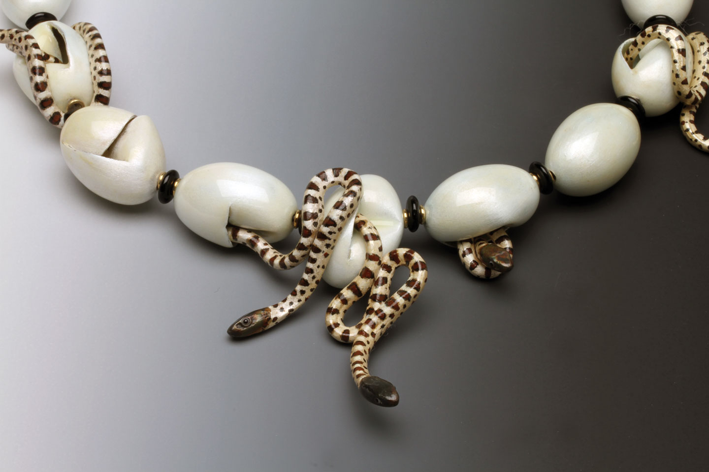STUDY OF NORTHERN BLACK RAT SNAKE NECKLACE, closeup showing eggs and hatchlings, of enamel over fine silver, with gold jumprings and Czech glass beads. Multiples of this necklace have been made from 1984 to 2000, his only limited production design; this necklace is 24.1 centimeters long, with eggs 2.7 cm each. The late Barbara Rockefeller owned the first snake egg and hatchling necklace made by Freda.  Mobilia Gallery Collection.