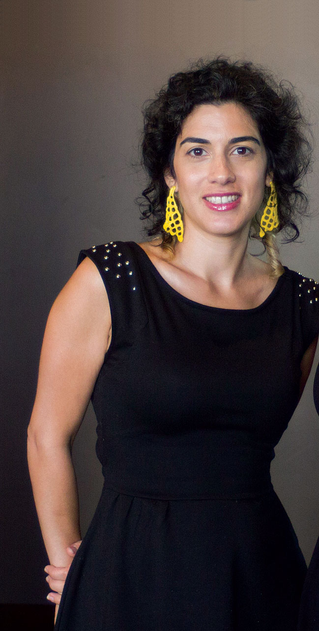 TAMAR NAVAMA   wearing one of her earrings, in yellow plastic, brass and silver.  Photograph by Erin C. Turner.