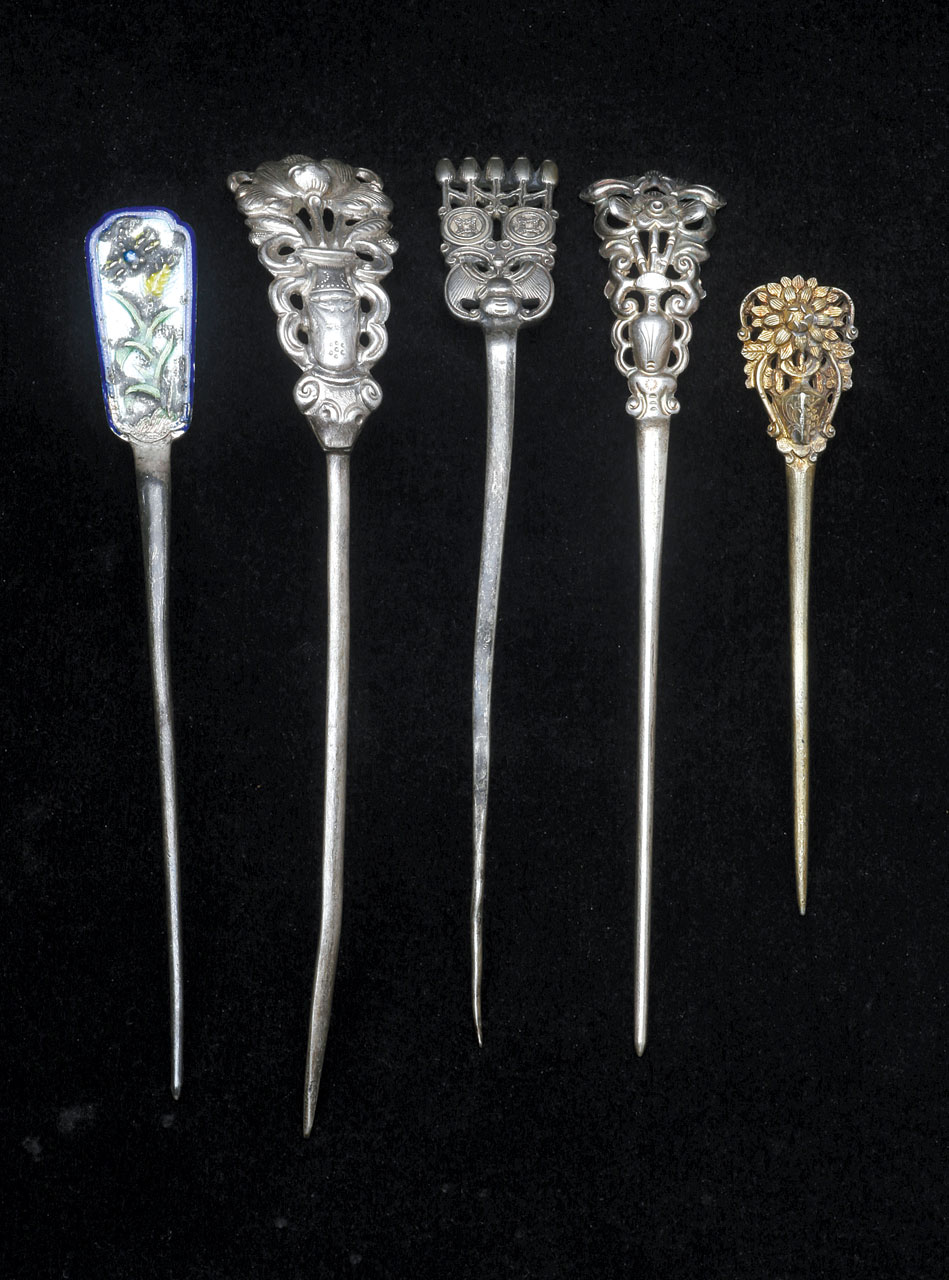 SILVER HAIRPINS WITH FLAT TOPS THAT REPRESENT FLORAL AND FAUNAL MOTIFS, which are either diestruck or cast. One is additionally gilded, another enameled. Some are cast or diestruck as one piece, others have been soldered together. These range from 7.9 to 12.6 centimeters long.