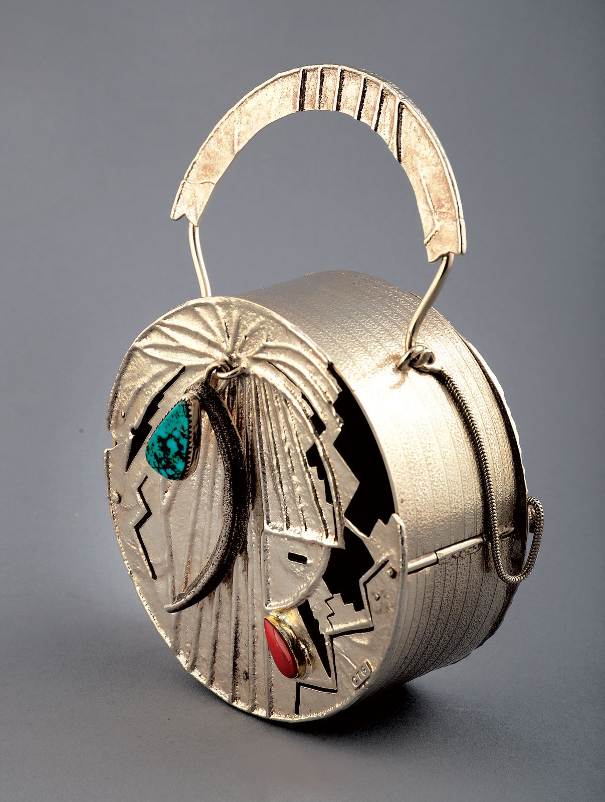 CASINO LOOT BAG by Connie Tsosie-Gaussoin of sterling silver, bezel set Royston turquoise, Italian coral in gold bezel, tufa cast feather design with fabricated silver sheet, 2012.  Photograph by Carolyn Wright.