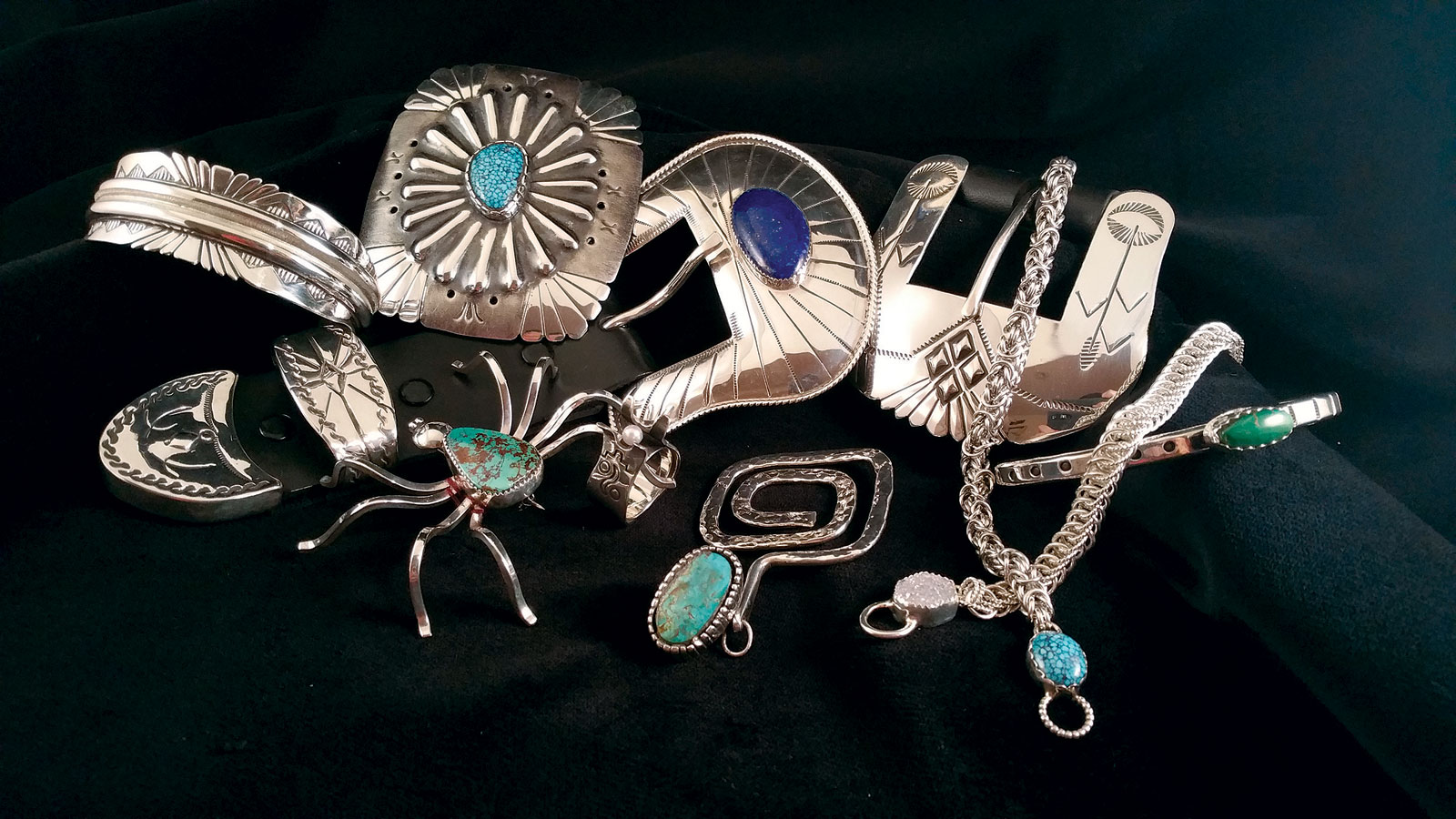 JEWELRY BY JERRY E. GAUSSOIN JR.  (left to right, top to bottom) : Navajo Mother Earth bracelet, 2017; Navajo Four Cardinal Directions concho style buckle, 2017; Ranger belt buckle, 2015; Simplicity cuff, 2017; Navajo Spider brooch, 2014; Pueblo Protector ring, 2017; Pueblo Maiden pendant, 2017; Byzantine Chain bracelet, 2017; and Half Persian chain bracelet, 2017. All jewelry is fabricated, some hand-stamped, formed and/or textured, set with turquoise or lapis.  Photograph by Jerry E. Gaussoin Jr.