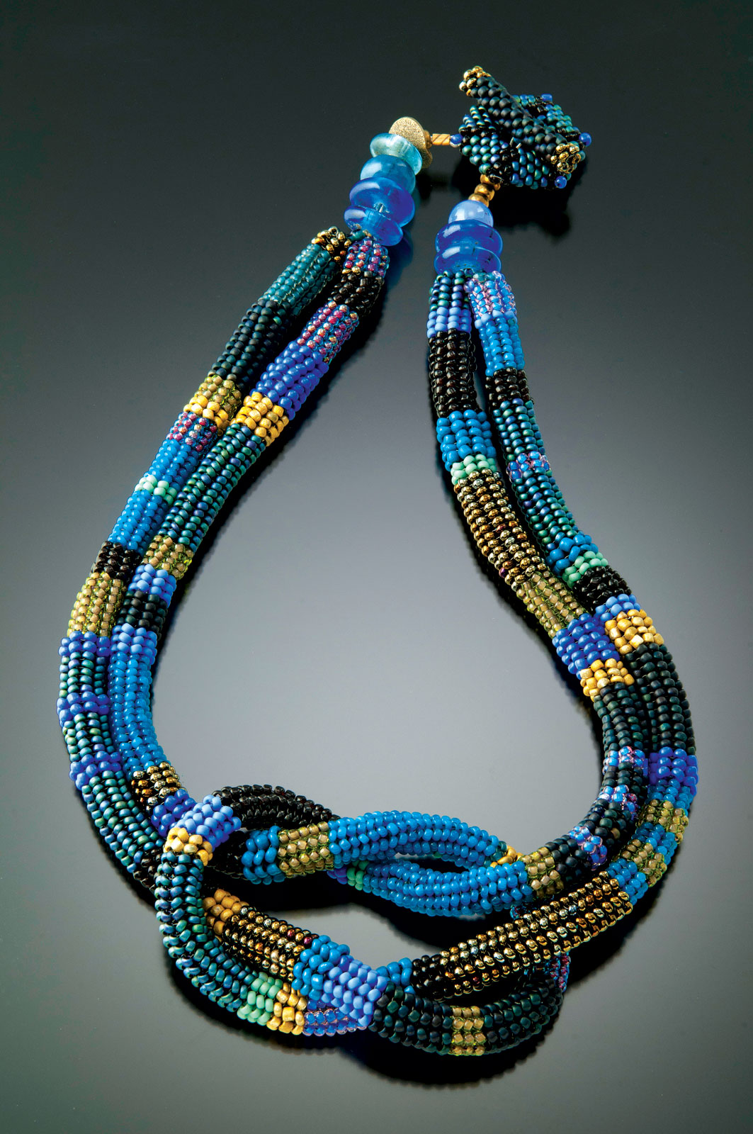 WISTERIA AND LEAF SQUARE KNOT NECKLACE of glass beads, woven in a spiral herringbone stitch with a needle and fishing line. The hollow tube is filled with small glass beads and then knotted into a square knot form; with recycled glass, stone beads and handwoven toggle closure, 45 centimeters long x 5 centimeters high, 2014.