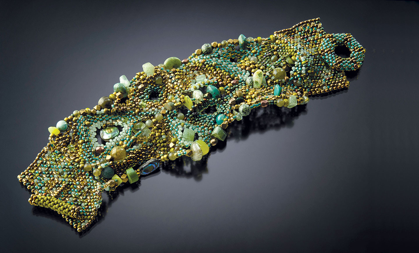 LEAFY TANGLE CUFF of glass seed beads and stones, woven in a free-form style between wire armature, with a needle and fishing line; includes turquoise, prehnite and jade, 17.0 centimeters long x 4.5 centimeters high, 2014.