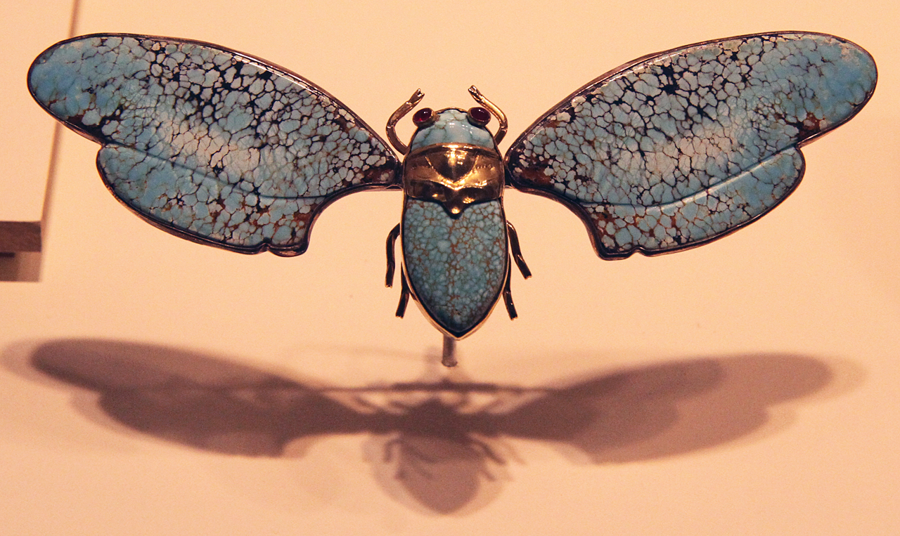 Contemporary cicada brooch of turquoise and gold (?) by Liz Wallace; note how the shadow enhances the appearance of this jewelry, seemingly suggesting that it is in flight. Cicada imagery in jewelry was used by both ancient Hohokam and Navajo (Liu 1998, 2001). The cicada is among Wallace's favorite insects and also of importance in Chinese culture.