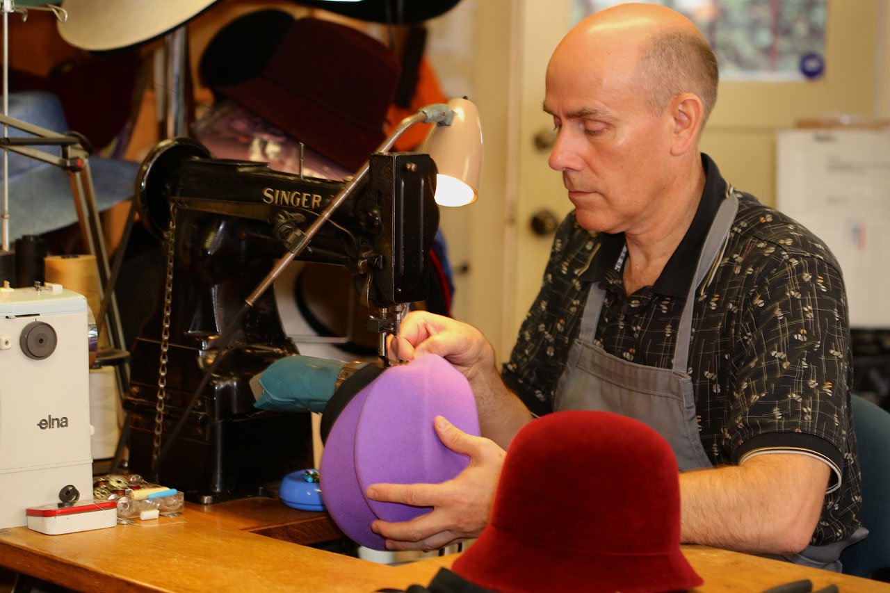 WICHERN using the Singer cylinder arm sewing machine to sew a head-size ribbon into the hat.  Photograph by Jason Wells.