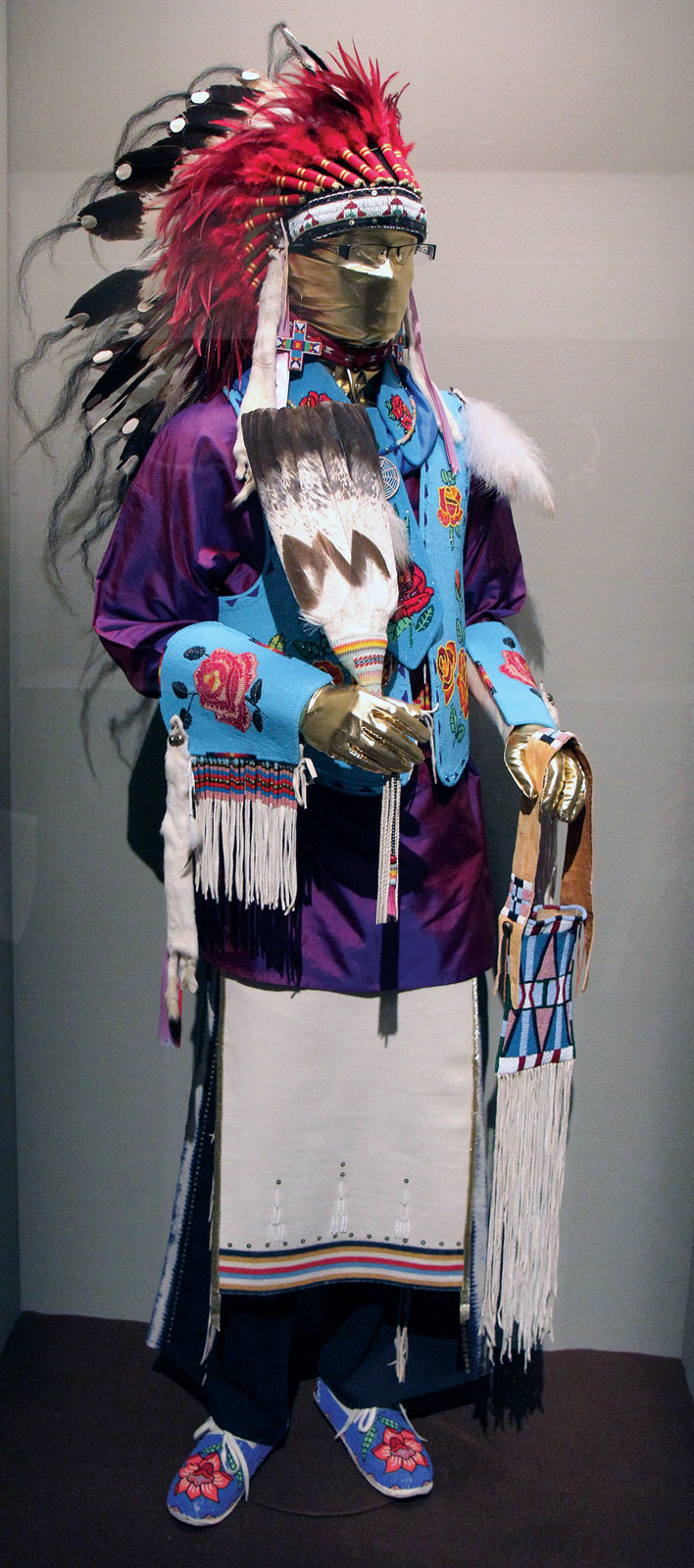KEN WILLIAMS POWWOW REGALIA, consisting of headdress, choker, vest, collar, tie, belt, shirt, breechcloth, leggings, beaded mirror bag, and Eagle tail fan that were provided by Williams's many friends. Williams is Northern Arapaho and Seneca.  Photograph by Ornament.