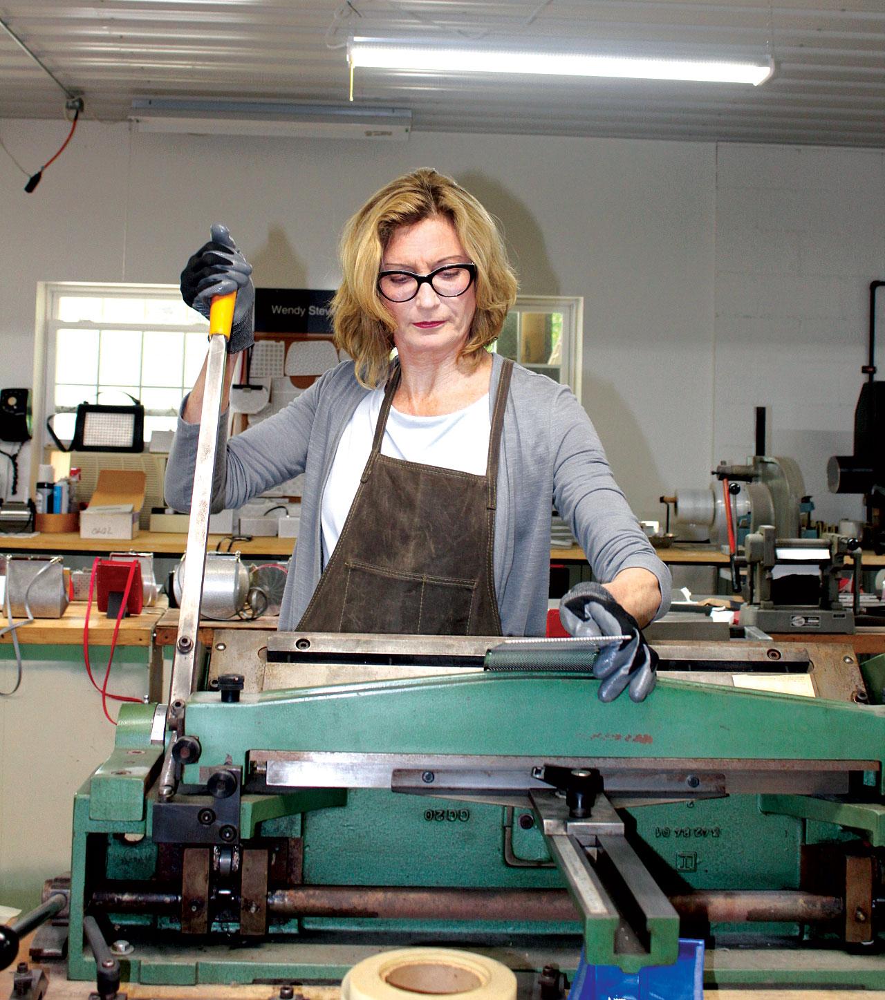 WENDY STEVENS at her hand shear cutting sheet metal.  Photograph by Dariel Benton-Updike.