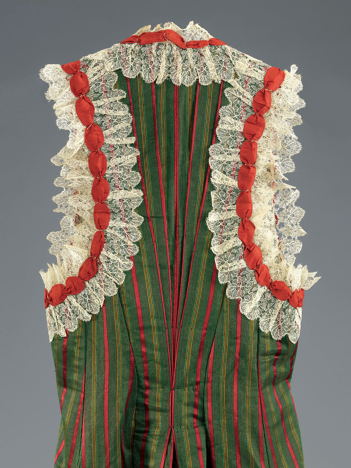 DETAIL OF A WOMAN'S ENSEMBLE of silk satin with cotton lace and silk ribbons, blouse with silk-thread embroidery, Tlemcen, Algeria, early twentieth century.  Photograph by Mauro Magliani, courtesy of The Israel Museum, Jerusalem.