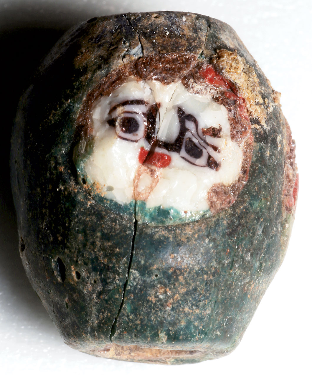 GREEN BARREL BEAD WITH TWO FACES, found in Nubia; faces appear to be a version of Gorgon, but not seen before. Brown glass may denote hair. The face cane shown is battered and of very white glass. This bead (21.12473.4) was found with the eyebeads with gold foil or bands on the last page.  Courtesy of the Museum of Fine Arts, Boston.