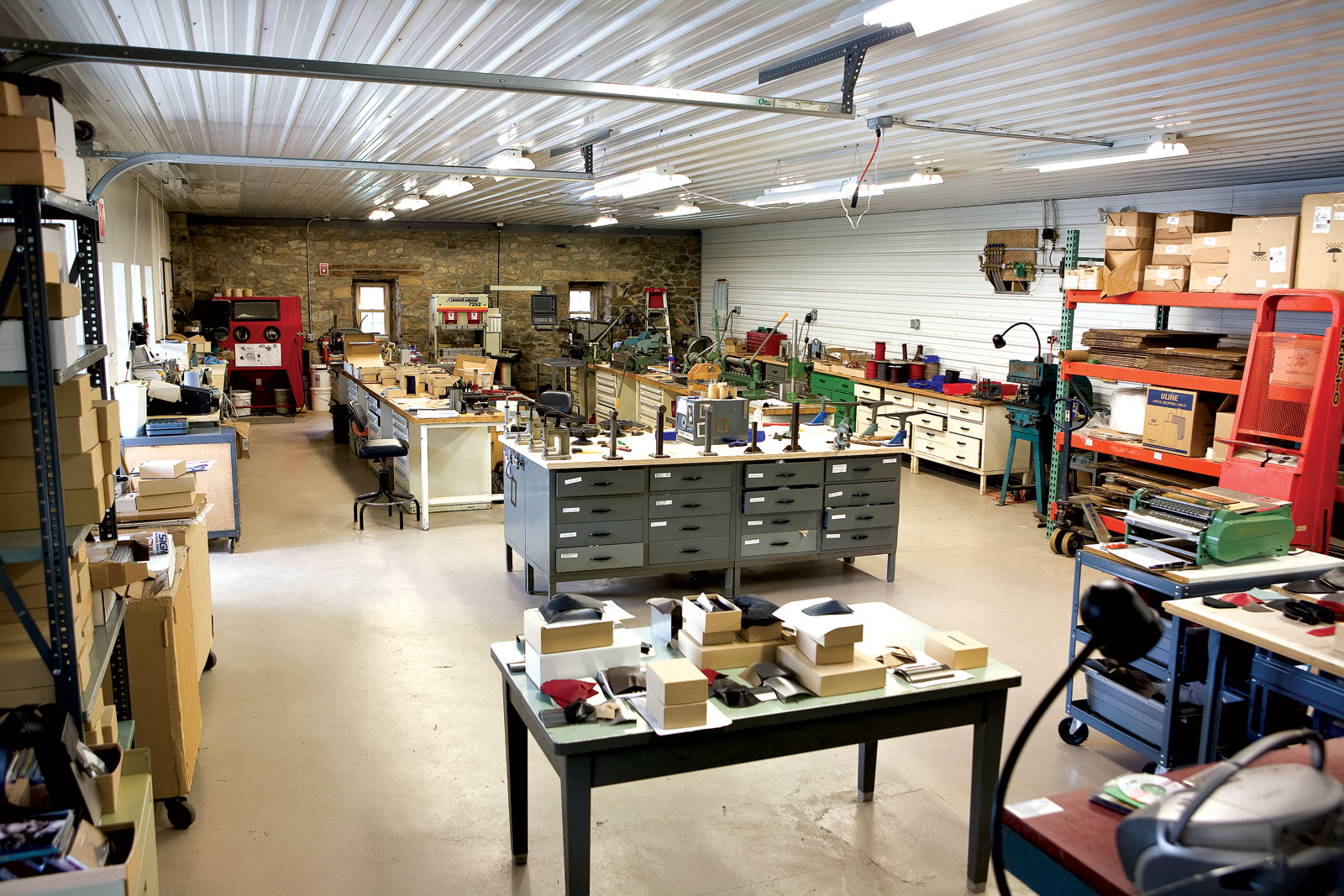 WENDY STEVENS STUDIO.   After the studio fire in 2004, the facility was redesigned and rebuilt on the main level of the stone barn on her eight-acre farm property. In the foreground is a packing table with finished pieces. To the right is the leather cutting table with a gluing machine. Directly behind the packing table is the stake bench where the pieces are assembled. Against the wall are the orange pallet racks where sheet metal is stored with a hydraulic lift. In the background are the tool benches with slip rolls, notchers, shears, a hand press brake and a hydraulic brake, a sand blast cabinet and deburring wheels.  Photograph by Kate Lacey