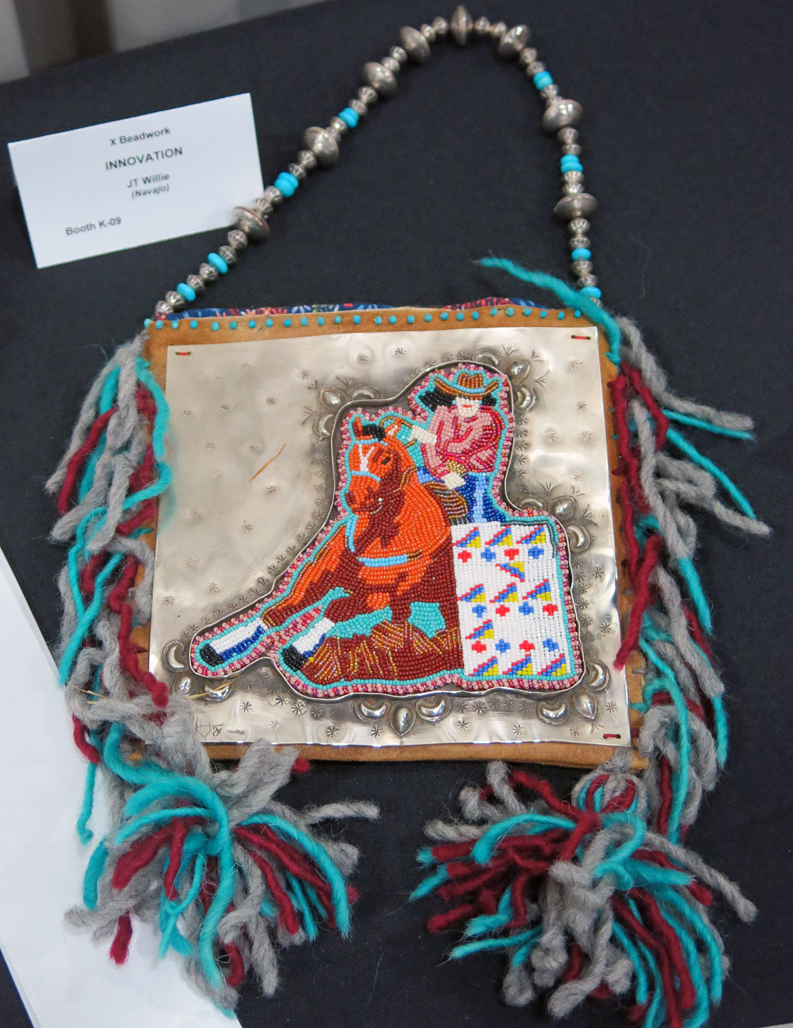 "BEADWORK BAG made by JT Willie (Diné), who received the Innovation award in the Beadwork category. This stunning piece features stamped silver and a horse and rider emerging from behind a rug pattern. Such beadwork is the subject of ""Beads: A Universe of Meaning"" at the Wheelwright Museum in New Mexico, recently featured in Ornament Volume 40.2.   www.wheelwright.org   www.ornamentmagazine.org/shop/ornament-print-edition-volume-402"