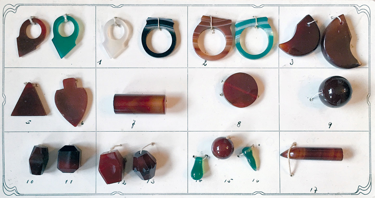 GEBRÜDER WILD COMPANY BEAD SAMPLE CARD, showing a wide range of Idar-Oberstein agate ornaments, including some rarely seen in the African trade. The top row displays  talhakimt ,  turmrings  and simulations of feline claws.