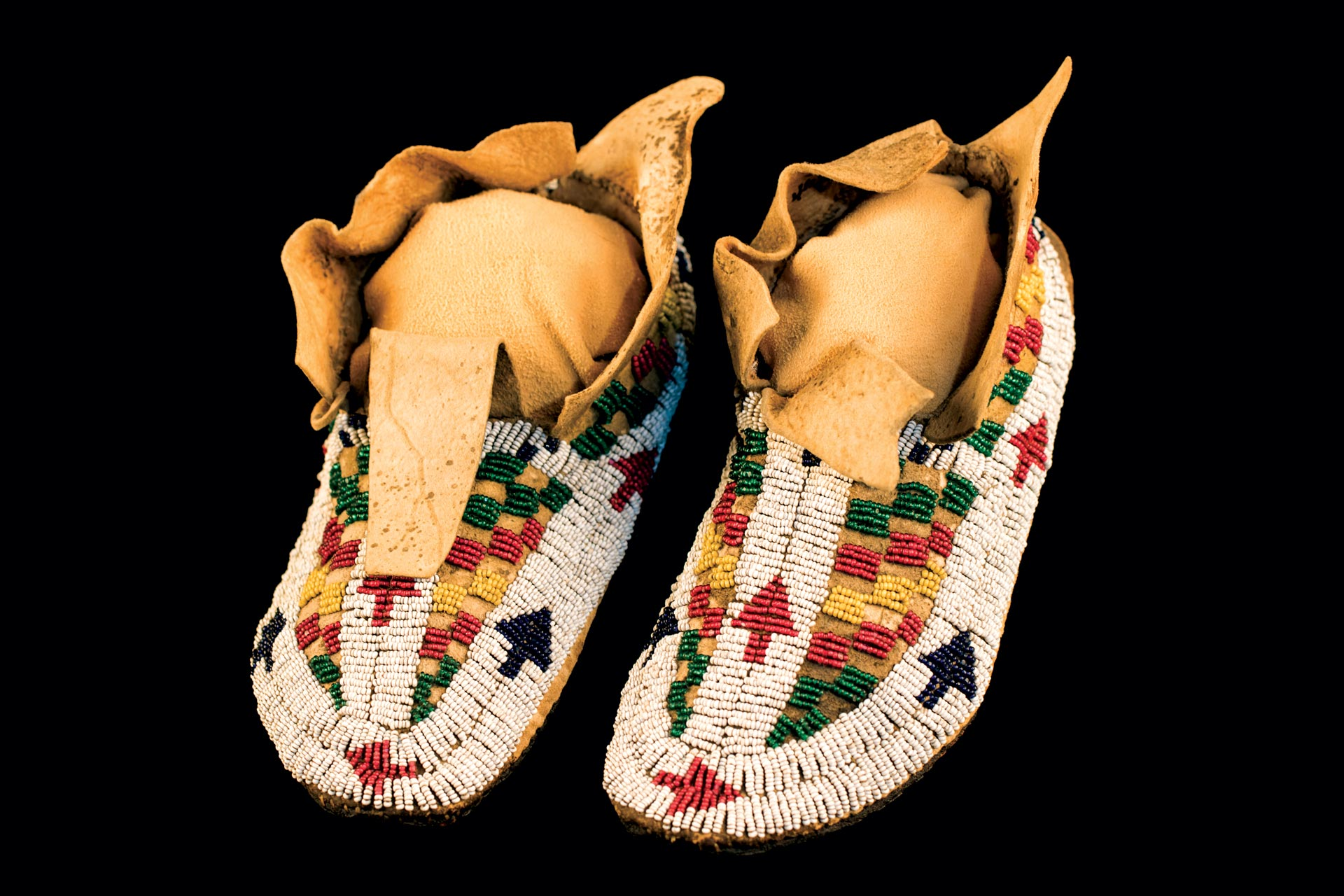 BOY'S MOCCASINS (Northern Cheyenne) of buckskin, rawhide, glass beads, sinew, 1875-80. The small and somewhat irregular white beads on these moccasins help date them.
