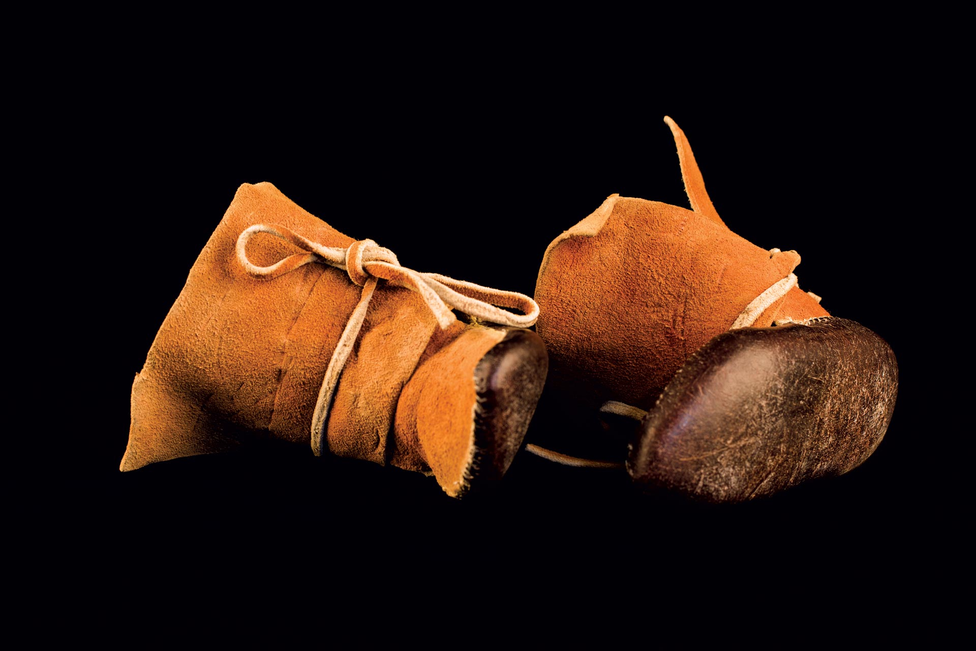 BOY'S MOCCASINS by Santiago Romero (Jemez) of leather, sinew, vegetal dye, 1950s.