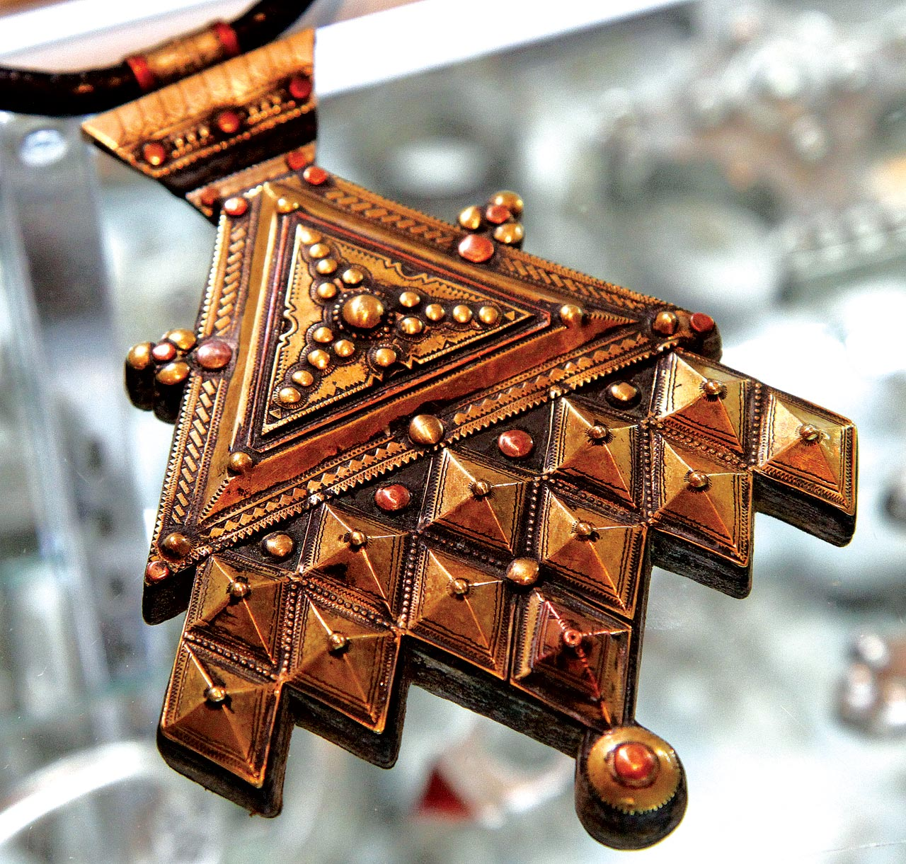 CONTEMPORARY VERSION OF TRADITIONAL TUAREG HAMSA/KHOMESSA. Niger, fabricated, of brass, copper and leather. It is the melding of a triangular amulet and a doubled hamsa, although with two more elements, so as to make the design symmetrical. Both the triangle and hamsa offer protection. While this pendant is new and in base metals, there is still a good level of crafting.  Courtesy of Ethnic Embellishments.