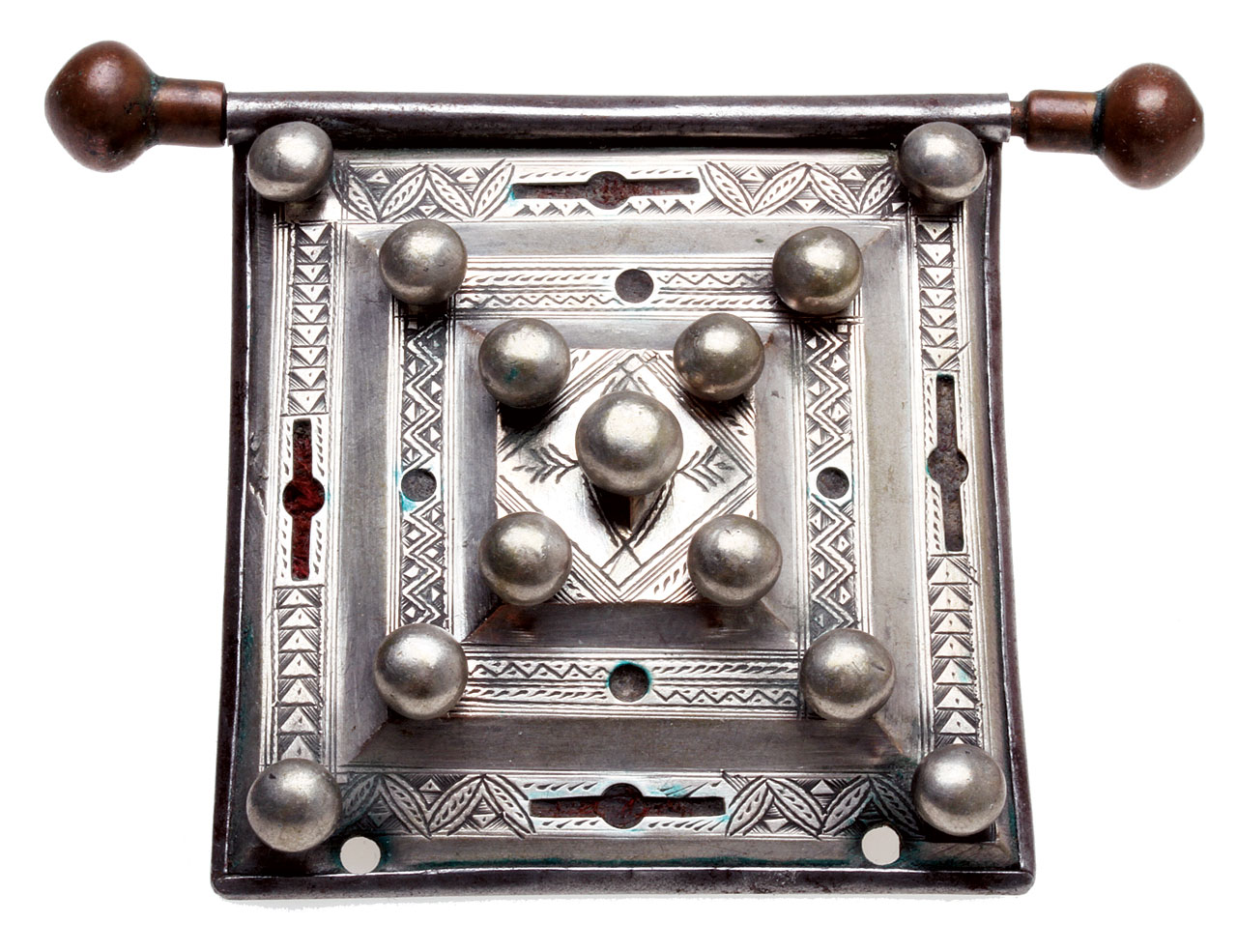 BEAUTIFUL MAURITANIAN OR TUAREG AMULET, of silver, copper with steel back; it has cutouts that once held red and most likely green-colored material, now too faded to determine their original color. The silver balls are decorative, as the stepped front is held onto the steel back by bezels, not rivets. Note the fine engraving. The pendant/amulet is 5.7 centimeters wide, not including the hanger.