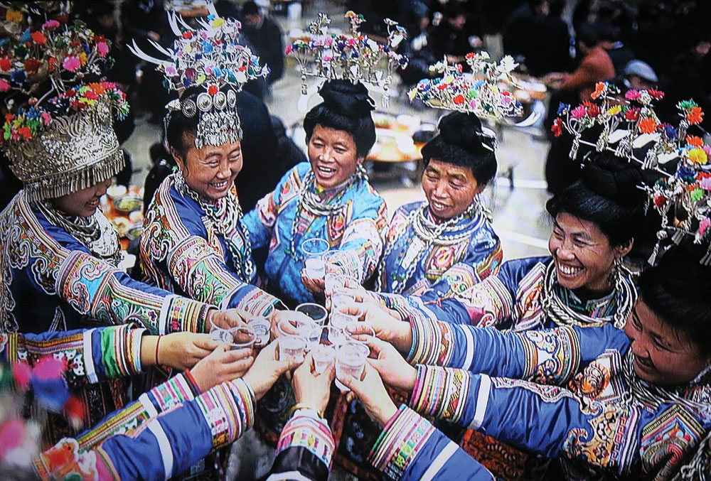 "MIAO WOMEN enjoying a New Year celebration, part of a slide show in the ""Vanishing Traditions"" installation. They are likely saluting each other with  baijiu , a noted clear liquor."