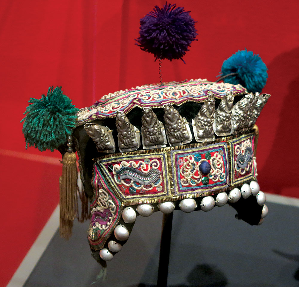 DONG CHILD'S HAT, decorated with pompoms and the eight Daoist immortals, of cotton, silk, silver alloy, embroidered, Liping or Rongjiang County, Guizhou Province, China, mid-twentieth century.  Photograph by Patrick R. Benesh-Liu .