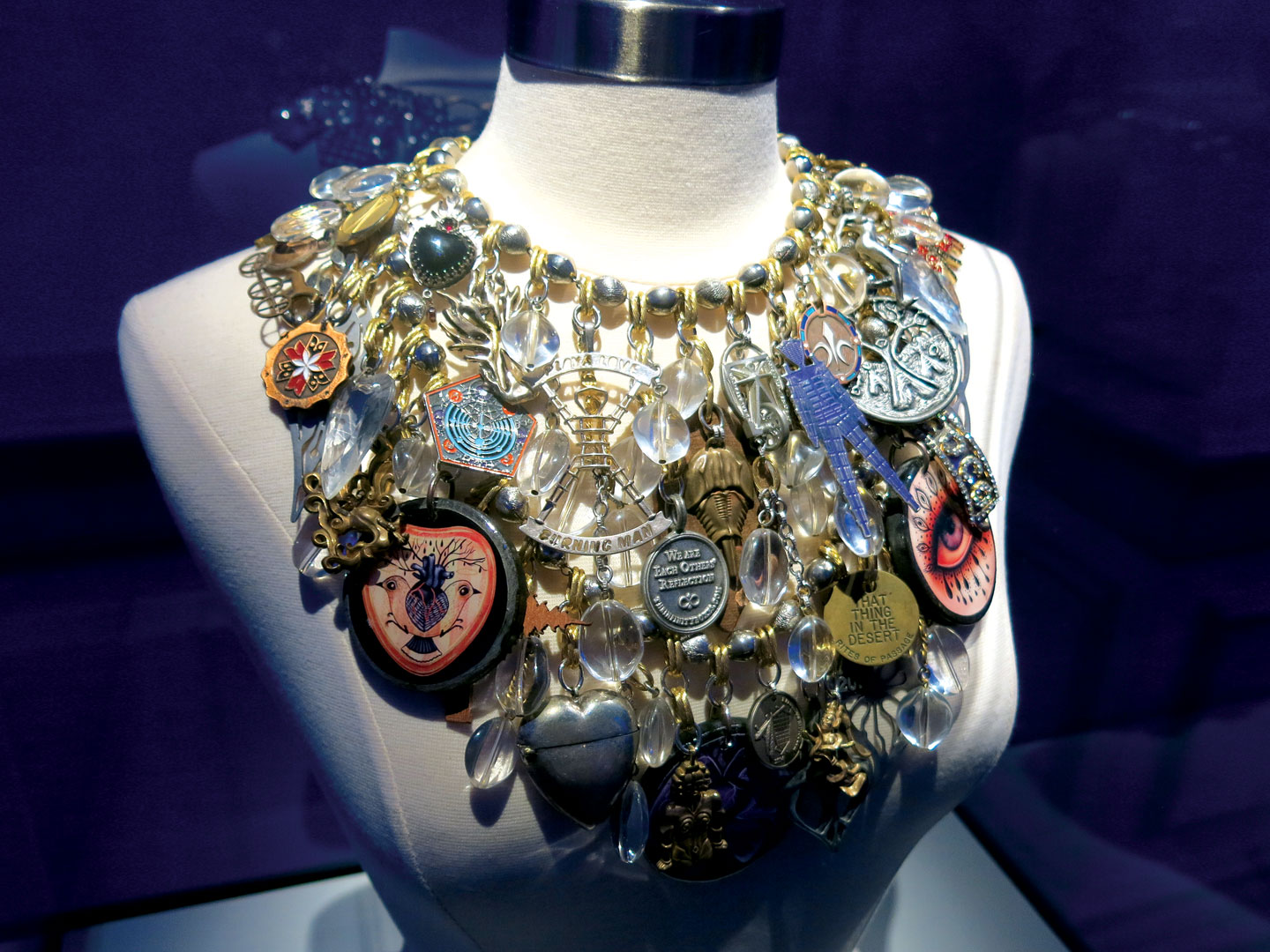 THE PLAYA PROVIDES NECKPIECE from various artists, assembled by Jennifer George, of metal, plastic, crystal, abalone, wood, and sterling silver, 2006-2017. The gifting economy that underpins the entire foundation of Burning Man, both literally and figuratively, leads to a continual and constant exchange of medals, pendants, badges, brooches, and other memorabilia as signs of affection, friendship, community, and shared memories.  Photograph by Patrick R. Benesh-Liu.