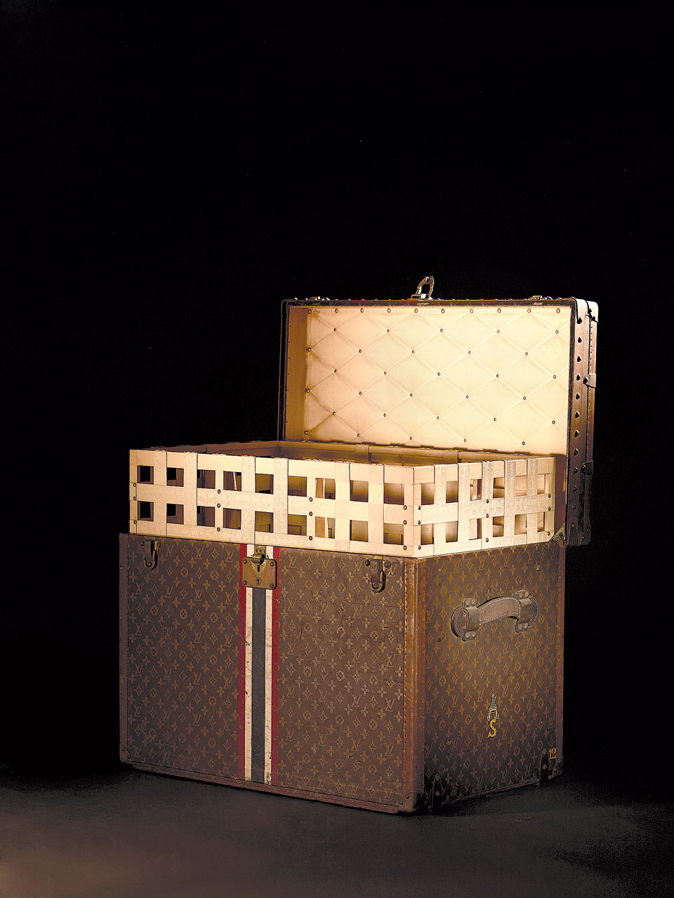 VUITTON HAT TRUNK. The Vuitton luggage ordered for Queen Sirikit was striped with the colors of the Thai flag and monogrammed with the Queen's cipher.