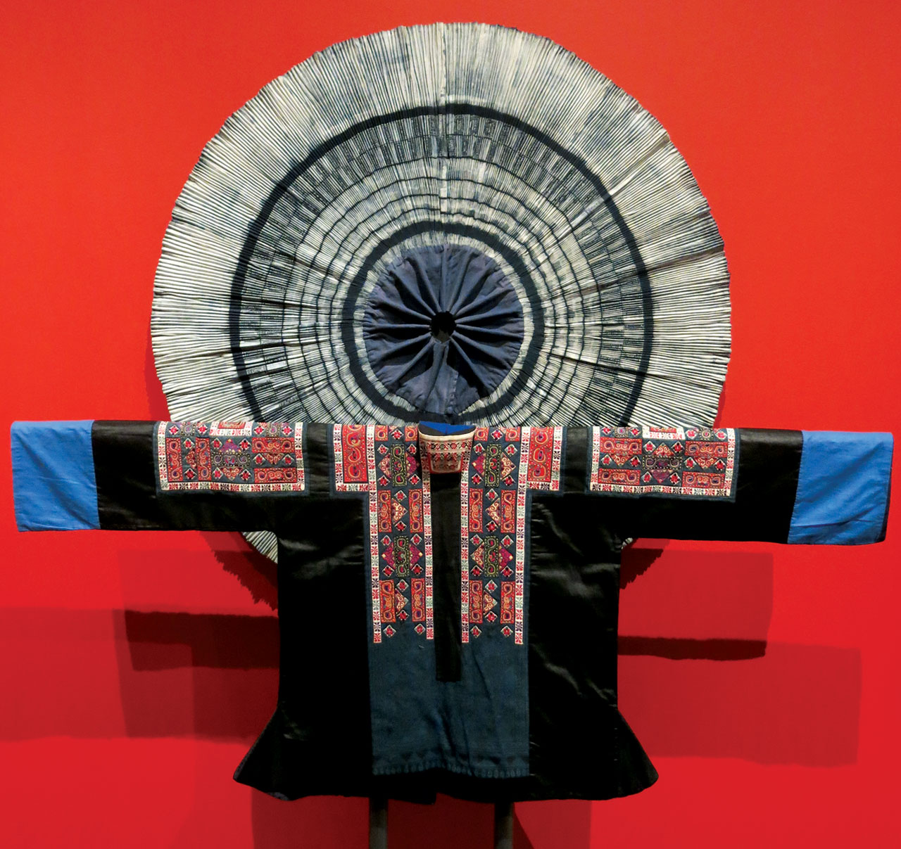 MIAO WOMAN'S JACKET of cotton and silk, embroidered, Guiding County, Guizhou Province, China, mid-twentieth century. Behind the jacket is a pleated, indigo-dyed Miao woman's skirt.  Photograph by Patrick R. Benesh-Liu.