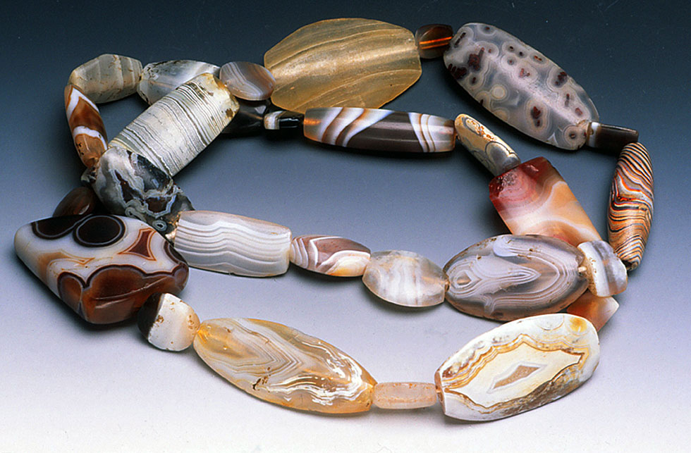 Strand of ancient hardstone beads from Afghanistan, primarily tabular, with modern stringing; note the beauty of the stone patterns as revealed by their ancient makers. RKL