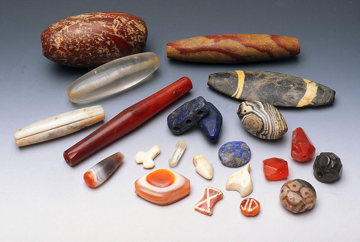 Assortment of ancient stone and shell beads from Afghanistan, including etched beads, agate and carnelian. Note lapis beads, including spacer, very clear quartz crystal bead showing perforation and quartz crystal, pierced at top as pendant. RKL