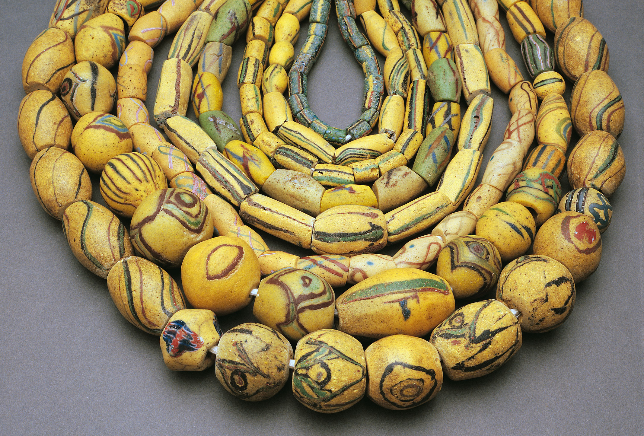 Assortment of Ghanaian powder glass beads, primarily adjagba types, many with cruciform decorations and preformed elements, both indigenous and European. Largest bead ca. 5 cm long. Courtesy: Picard Collection. RKL