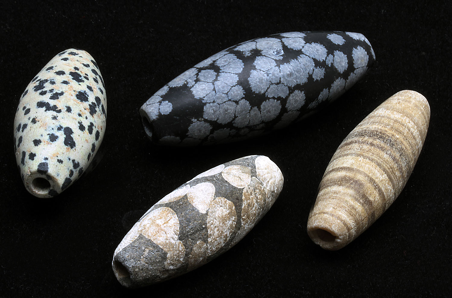 Two contemporary Afghan beads from 2000, one of snowflake obsidian, versus two ancient ones, lower one of fossilized coral; largest 5.1 cm long. Courtesy of Beadazzled. RKL