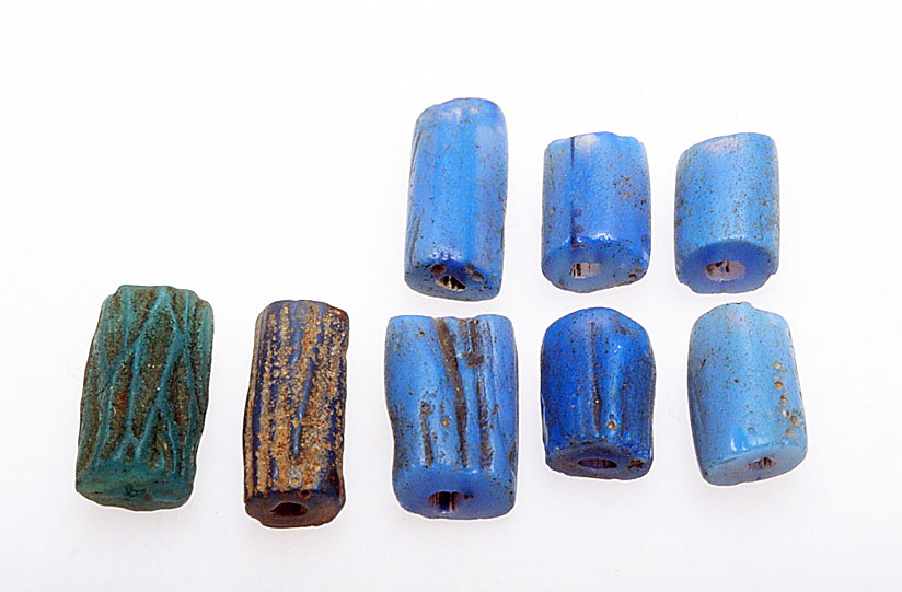 An array of dichroic, corded beads from Nigeria (6 medium blue on the right) and their Czech imitations on the left; the longest are 1.5 cm. The imitations are pressed or molded and are not of dichroic glass. RKL