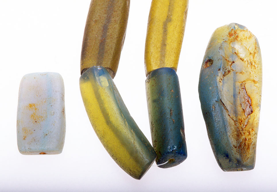 The same array of Nigerian dichroic glass beads photographed with both reflective and transiluminated light; the beads are now greenish-yellow, instead of varying shades of blue under only reflective light. RKL