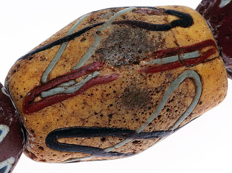 An akoso powder glass bead, with a worn surface, so that the gray glass core shows partially; it is decorated with preformed glass threads. See Ornament issue 25 (2), Winter 2001, still available as a printed copy or pdf for detailed information on African powder-glass beads. RKL