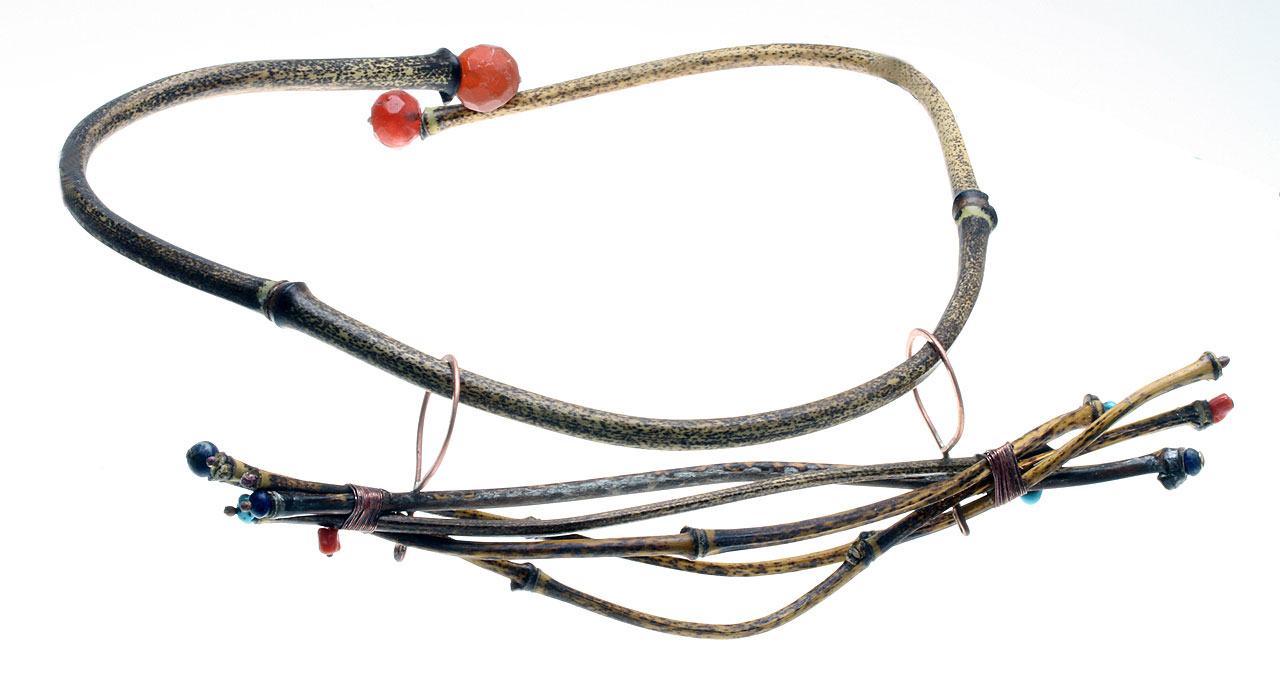 HORIZONTAL JIGGED PENDANT ON BAMBOO TORQUE, with faceted Czech glass beads as terminals on torque; pendant hangs from two soldered, forged copper loops. Pendant has been wire-wrapped and the ends decorated with semiprecious stone beads or melted copper balls. Because heatbent black bamboo retains its pliability, the wearer can pull the ends apart when fitting it onto the neck.