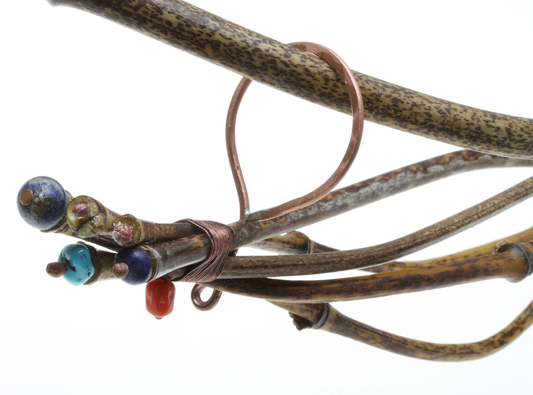 DETAIL OF SUSPENSION LOOP AND ENDS OF HORIZONTAL PENDANT. Hole was drilled through bundled culms, end of loop inserted, then bent into circle to trap it in place. To add visual interest, ends of wirewrapping and ends of bamboo culms were decorated with lapis, turquoise or coral beads and copper balls; these sit in burred depressions. Because copper suspension loops are forged for strength and thus thin when viewed headon, the pendant appears to float beneath the toque.