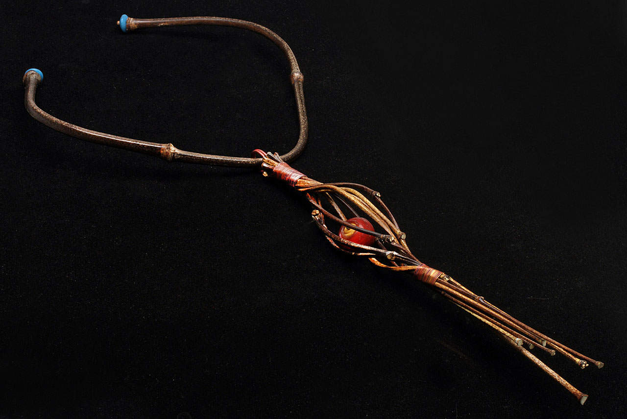 FINISHED TORQUE WITH VERTICAL JIGGED PENDANT; the torque is also terminated with vintage molded Czech glass beads from the African trade; these Czech beads also serve to prevent the pendant from coming off the torque, as the beads are larger than diameter of copper loop. The trapped Venetian bead inside the expanded space of the ten culm pendant freely moves. If you compare this pendant with earlier ones, you can easily see how much more basket-like they are, contrasted to those made without jigs.