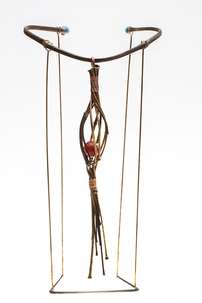 FINISHED TORQUE AND PENDANT ON FABRICATED BRASS STAND, showing how the jigged pendant hangs. Pendant is 27.7 cm long.