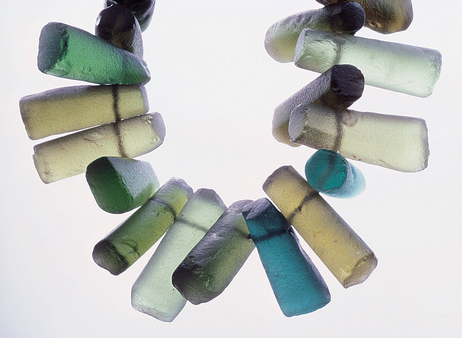Cold-worked pendants made by re-grounding and perforating pieces of broken bottles. RKL