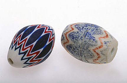 Contemporary polymer chevron replica (left) and Prosser imitation chevron, very worn, from the African trade (2.2 cm long). RKL