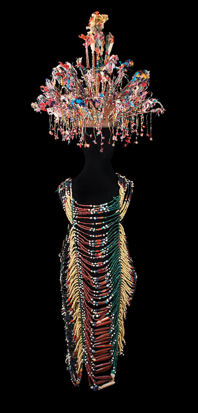 WEDDING OUTFIT (  ulu rajang  ), Iban peoples, Sarawak state, Borneo island, Malaysia. HEADDRESS of wood, paper, glass beads, cotton, sequins, 38.1 x 61.0 centimeters. DRESS of stone, glass and shell beads, 77.5 centimeters long, twentieth century.  David McLanahan Collection.