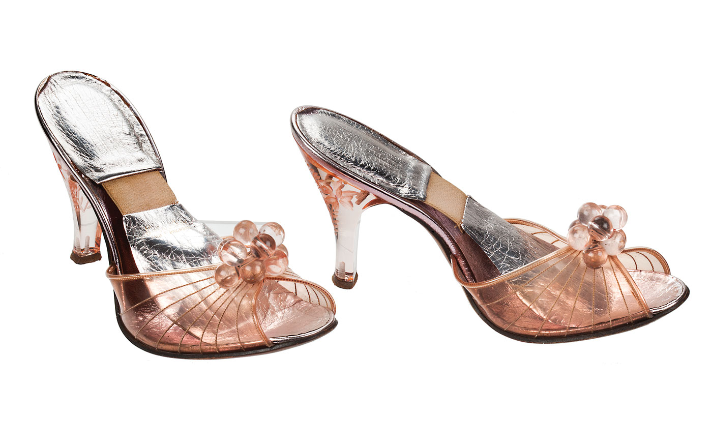 """Walk This Way:  PEEP-TOE MULES of plastic, lucite, leather, elastic Spring-o-lator, by Fenton Last, Saks Fifth Avenue, retailer, mid-1950s. These mules feature an innovation called the Spring-o-lator, a strip of elastic tape in the sole that helped the shoes adhere to the wearer's feet. The device was first popularized by Beth Levine (1914–2006), known as the """"First Lady of Shoe Design."""""""