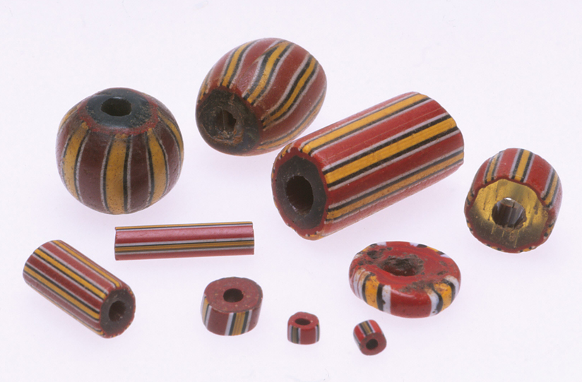 Various sizes and shapes of drawn cane beads, made from the same cane, but drawn to different diameters, cut and reheated. These are from the African trade. RKL