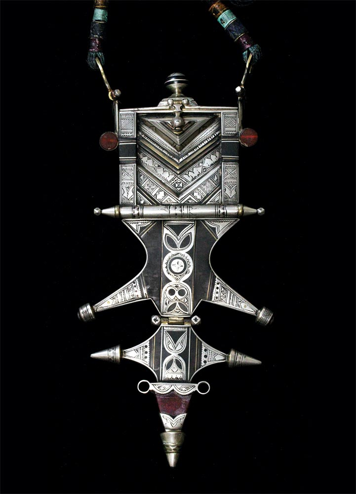 Tuareg Jewelry:  SPECTACULAR AND INTRICATE KORAN HOLDER, over one hundred years old, from Hoggar, Algeria, strung on leather cord, not visible in these images. It has been set with two round cabochons of agate, as well as a broken agate talhakimt, most likely all from Idar-Oberstein, Germany. Of silver inset into abaka wood, it is articulated with three hinges, decorated additionally with brass, 28.0 cm long. Finely and copiously engraved on obverse and reverse, it is most likely signed but I am not able to identify Tifinar signatures. The metal inlays into wood bear resemblance to that of other wood/metal jewelry but this is the most elaborate design I have seen of Tuareg personal adornment, combining almost all their design elements, done in impeccable metalsmithing. Perhaps the quantity and variety of really well-made pieces of jewelry from Hoggar, Algeria, mean that there was considerable patronage from wealthy Tuareg nobles living there in the past. Despite our ability to admire Tuareg techniques and designs, the experience would be so much greater if outside observers could decipher the hidden meanings in their jewelry, as hinted at in Fisher (1984: 194).