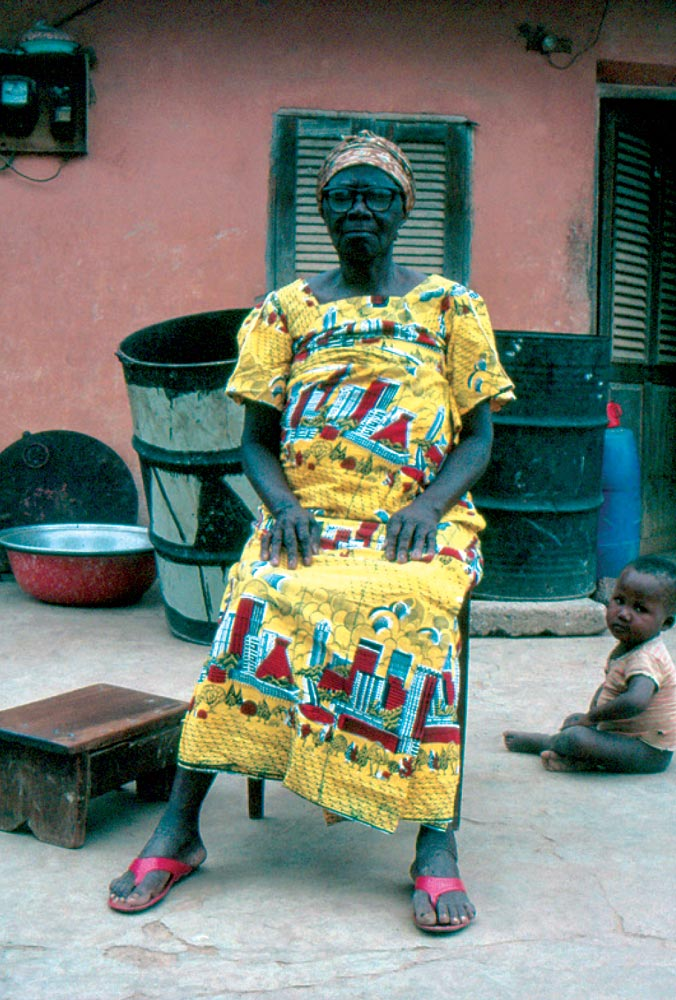 IN A VILLAGE NEAR BROBO, CÔTE D'IVOIRE,  an unidentified woman wears a wax-print featuring the distinctive skyline of Abidjan, 1992. The three-piece  complet , made from six meters of printed cloth, is considered by many to be traditional Ivorian dress and is associated with propriety, discretion, moral fortitude, and a high regard for tradition.  Photograph by Kathleen Bickford Berzock.