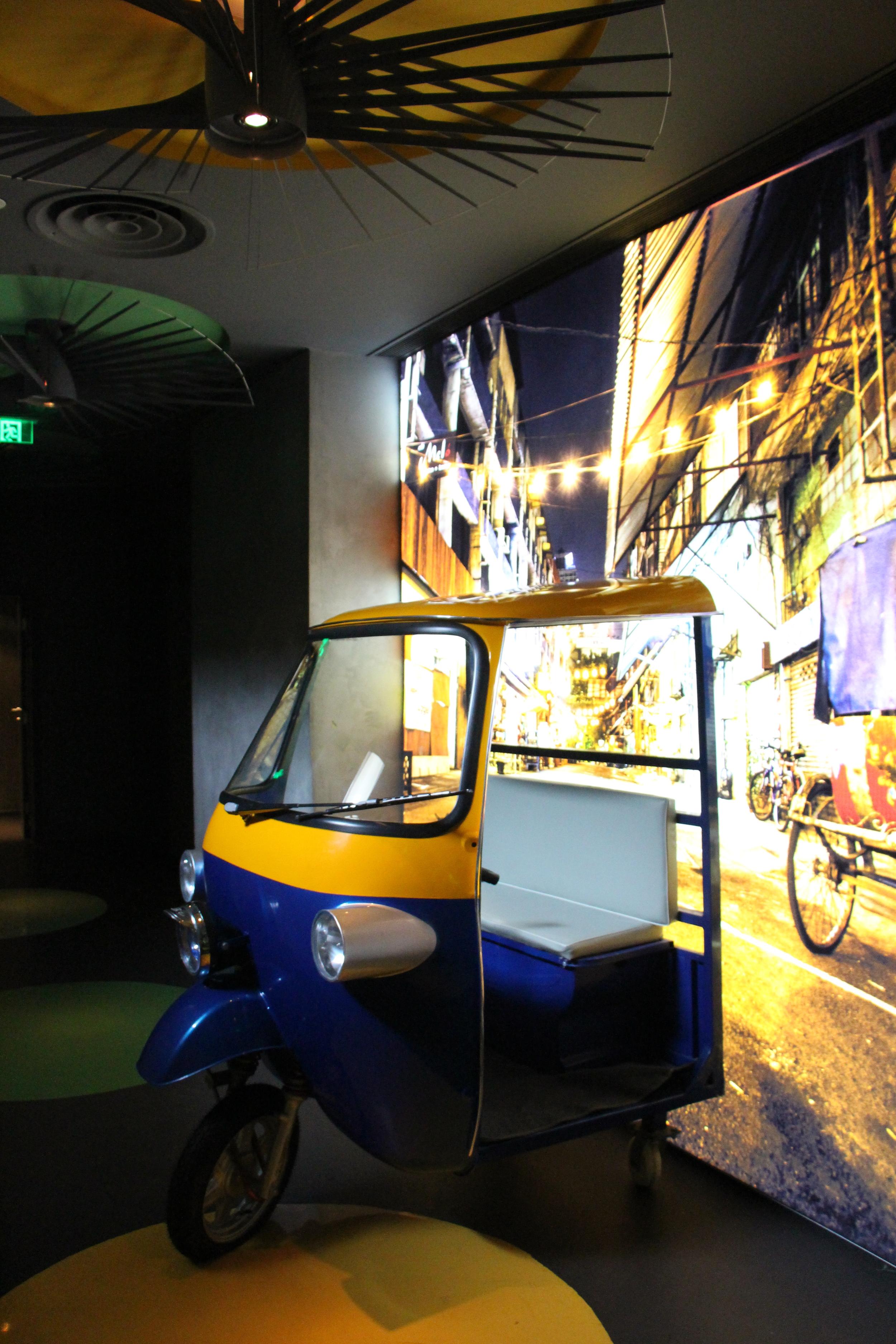 Half a tuktuk with a Bangkok background upon entrance