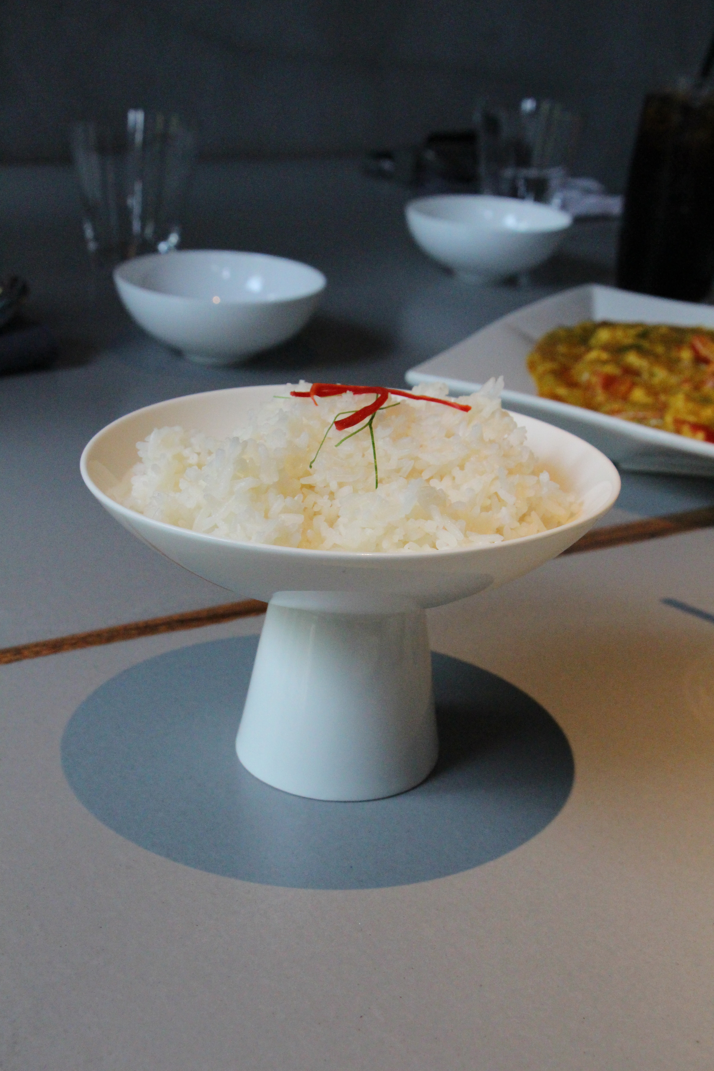 Small portioned rice, but is presented in an eccentric little bowl