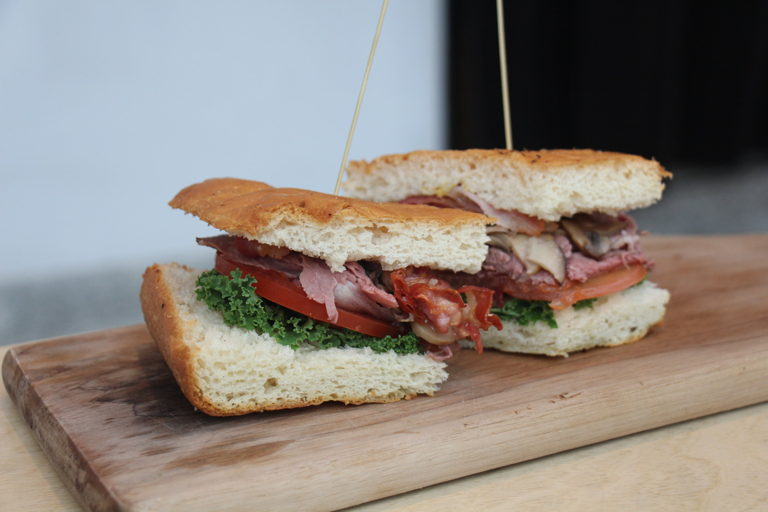 Thinly sliced roast beef served with mushrooms, kale, tomatoes and mustard sandwiched between two slices of crispy pancetta bread; highly recommended.