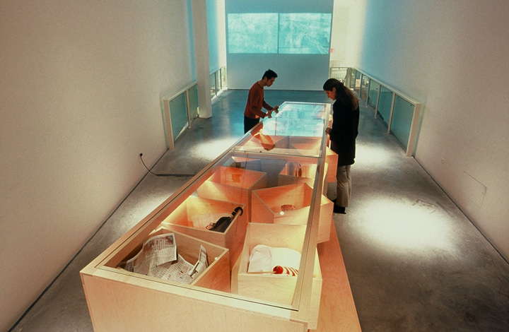 Visitors to the installation look through the top of the table section, through glass into the object boxes. The objects may be personal gifts or simply mementos of the experience.