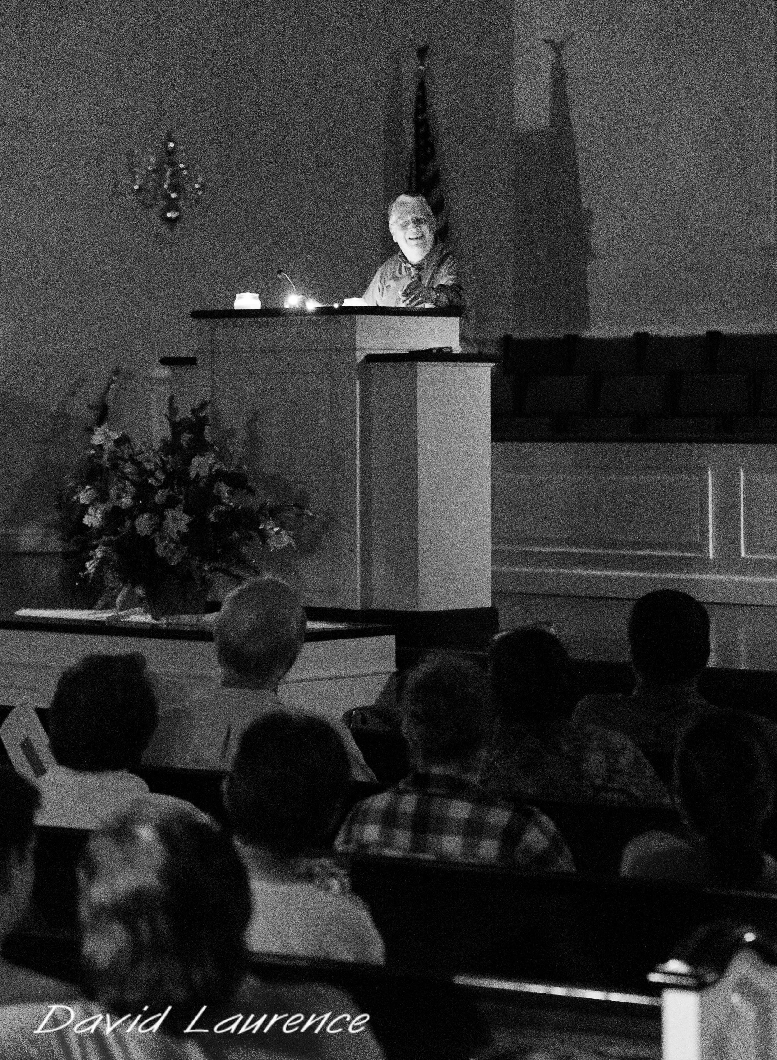 Brother Rob Pelkey preaching by flashlight. Bad storms rolled in during the 2013 camp meeting and the services were moved to the church. Shortly after the preaching started, the church lost power, but the preaching continued.