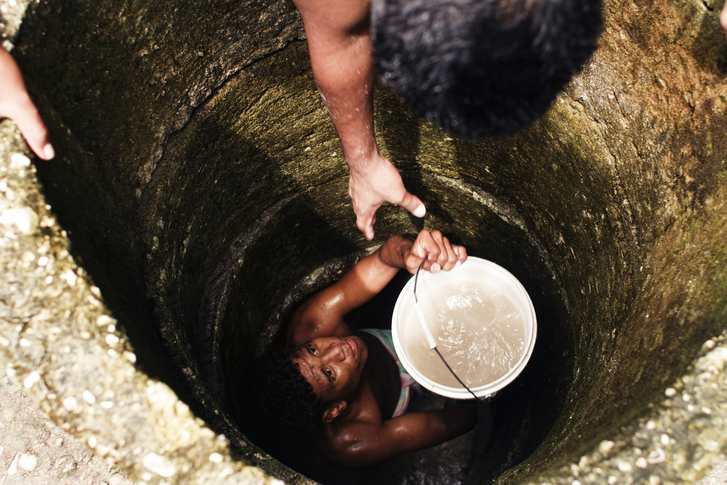 Island of Tarawa, Kiribati.A group of men emptying out contaminated water from a well. As sea levels have risen, many wells have become contaminated with salt water and can no longer be used.