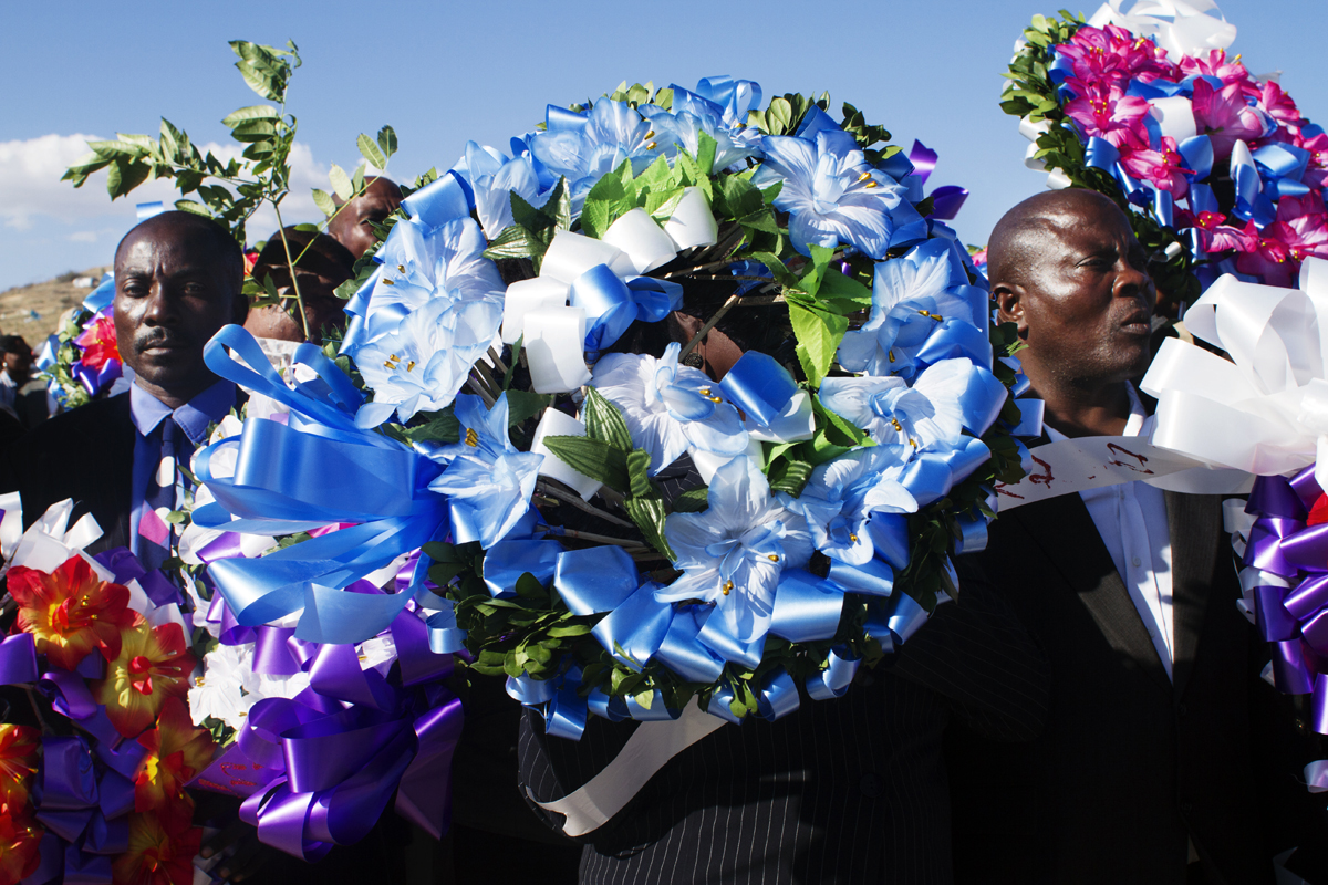A group of people with funeral wreaths to honor the dead in mass grave in Tit Tenyan. 2012.